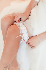 beautiful bride is sitting on the bed and trying the garter