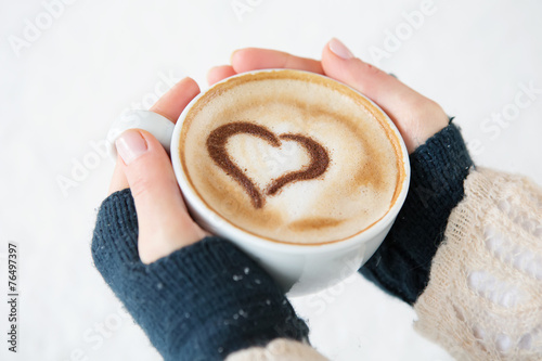 canvas print picture woman holding hot cup of coffee, with heart shape