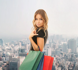 young happy woman with shopping bags over city