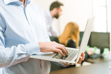 Happy young businessman using laptop in business office
