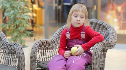 Girl sitting on a chair made of twigs with an apple in his hand