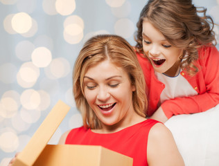 happy mother and daughter opening gift box