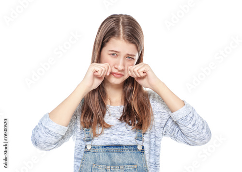 Crying young teenage girl in jeans overalls isolated - 76500520