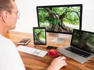 Mann mit vernetzten Computern und Mobilgeräten