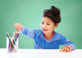 happy school girl drawing with coloring pencils