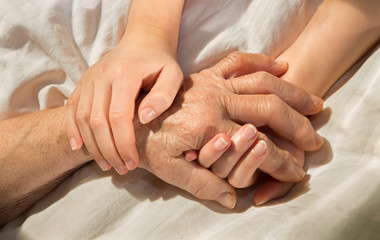 hands of grandmother and grandchild in the bed