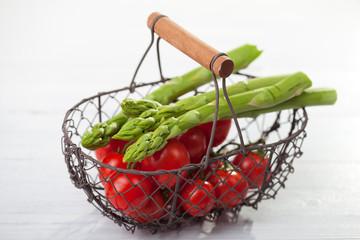 Drahtkorb mit Tomaten und Spargel