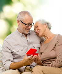 happy senior couple with red gift box