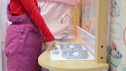 Girl playing with a toy kitchen turns on a gas stove