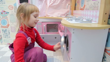Girl playing with a toy kitchen with a washing machine