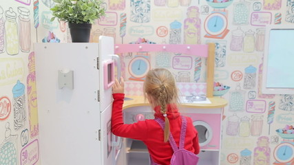 Girl playing with a toy kitchen opens the oven in the play area