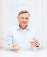 old man with pills ang glass of water