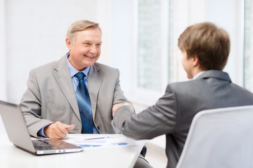 older man and young man shaking hands in office