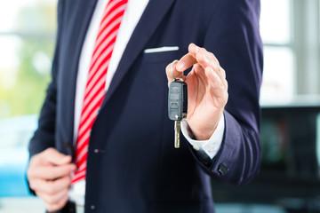 Verkäufer mit Autoschlüssel im Autohaus