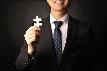 ジグソーパズルのピースを持っているスーツのビジネスマン男性