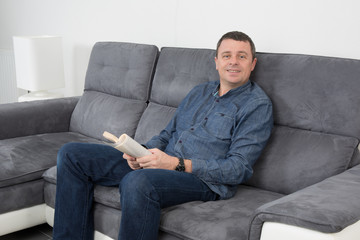 Homme sur son  sofa avec un livre dans les mains
