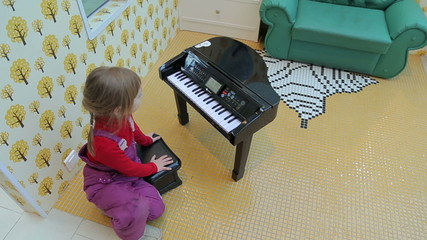 Girl playing on a toy piano in a children's recreation area