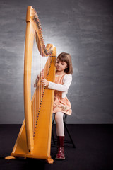 Little girl playing harp