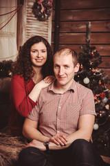 wife embraces her husband sitting in the New Year rustic interio