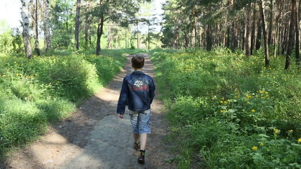 The boy is walking alone in the woods, shooting from behind
