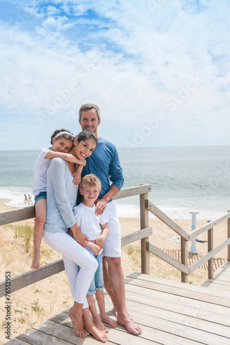 happy family  standing on a wood pontoon in front of the sea in - 76512953