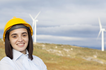 Portrait of a smiling female engineer standing at wind turbine s