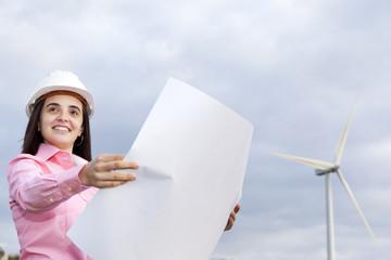 Female engineer holding a blueprint at wind turbine site