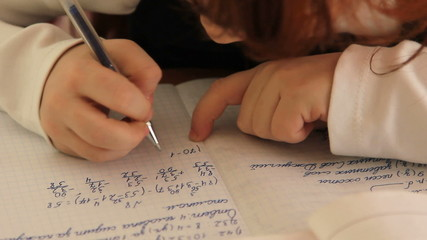 Pupil at the school writes in a notebook, performs  tasks