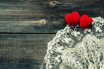 Wooden background with lace and red velvet heart