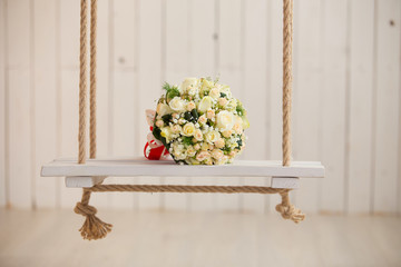 wedding rose bouquet of bride on wooden swing with rope