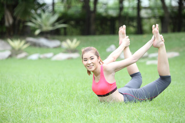 Yoga dhanurasana bow pose by asian woman on lawn