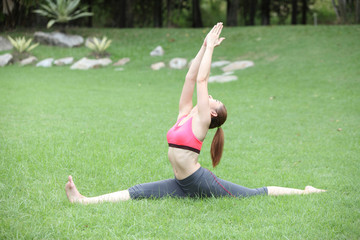 Young cute woman in the Hanumanasana/Monkey Pose on lawn