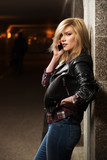 Young fashion blond woman in leather jacket calling on mobile ph