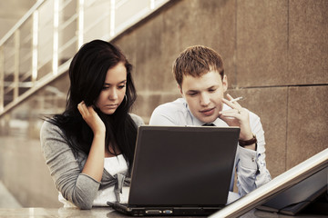 Young business couple with laptop