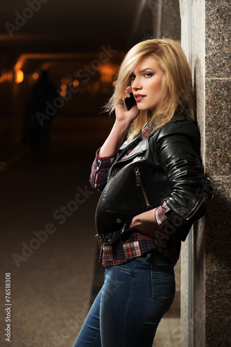 Young fashion blond woman in leather jacket calling on mobile ph - 76518308