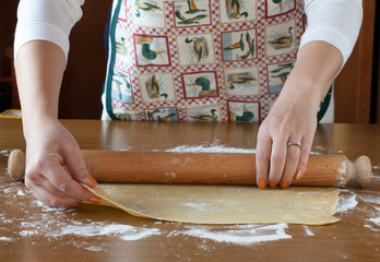Rolling Out Pasta Sheet On Wooden Table