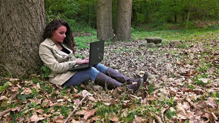 Happy female student with laptop in the park
