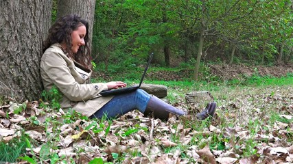 Teen student with laptop in a park