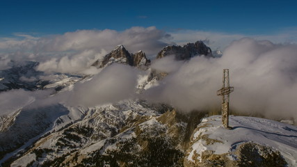 Cross on  Sella peak Sasso Lungo  in clouds Campitello resort