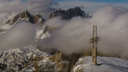 Cross on top of Sella peak, Sasso Lungo covered in clouds