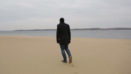 Sad pensive man walks along the shore of the Volga River