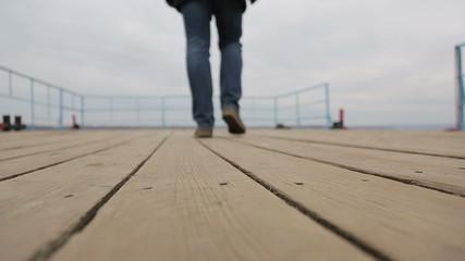 Sad pensive man walks on the pier, bottom view