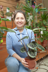 Happy mature woman with  Calathea plant