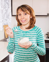 Smiling  woman eating boiled rice