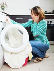 Unhappy woman cheking  clothes near washing machine
