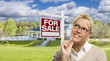 Young Woman in Front of For Sale Sign and House