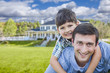 Mixed Race Father and Son Piggyback in Front of House