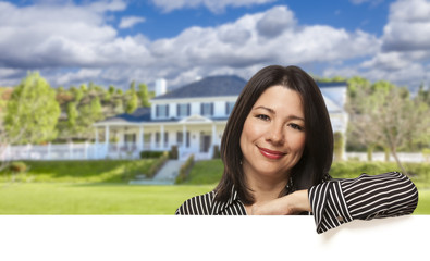 Hispanic Woman Leaning on White in Front of House