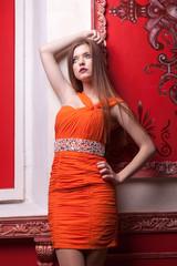 Woman in orange dress on red retro wall