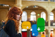 Portrait of young redhead woman inside public library.